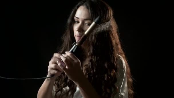 Smiling young woman curling her long brown hair with curler.