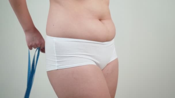 Woman with overweight measuring her thighs.