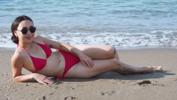 Nő a piros fürdőruha a strandon és a napozás.