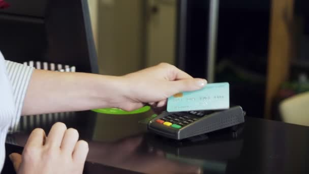 Žena klepnutí platební kartě na platební terminál.