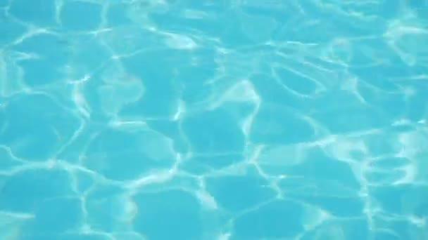 Zvlnění na modrou vodu v bazénu s odrazy světla.