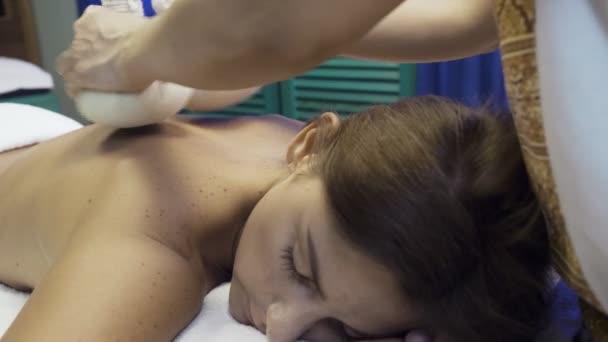 Frau bekommt Massage mit heißen Kräutertüten.