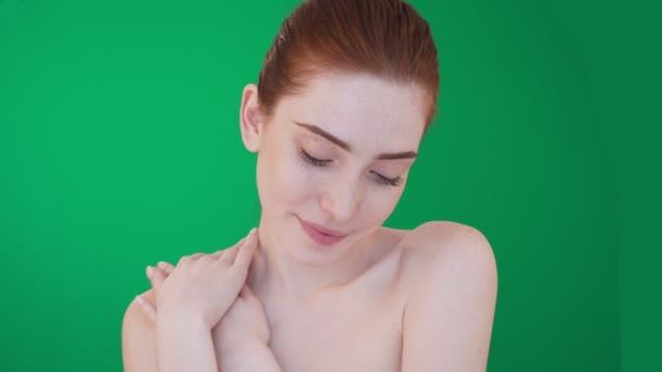 Žena v redheadu s úsměvem na kameře s nahými rameny.