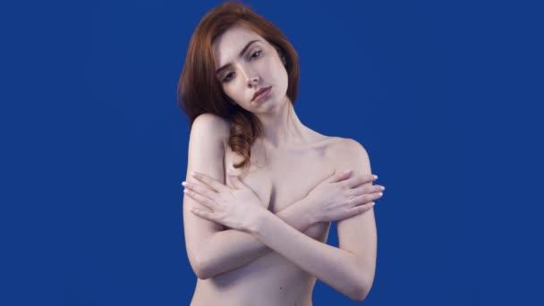 Fiatal vöröshajú nő pózol a kamera és a kísérti fedett mell.