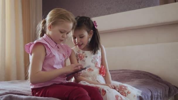 Két kislányok segítségével okostelefon ül az ágyon a hálószobában.