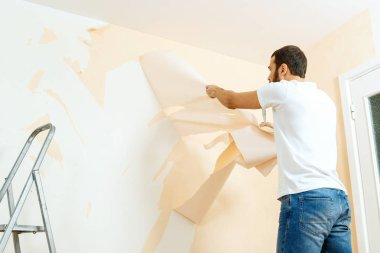 Man in with a scraper in the process of removing old wallpaper.