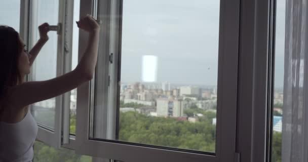 Redhead otevřela okno a v den volna si užívá čerstvý vzduch.