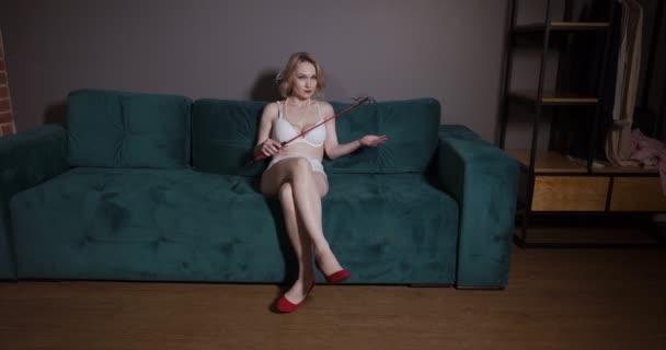 sexy blonde dominante Frau sitzt und wartet unterwürfig mit einer roten Peitsche.