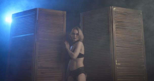 Sexy dominante Frau mit einer Peitsche erscheint aus der Holzplatte.