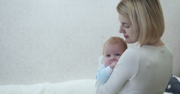 Mother carefully caresses her baby in her arms in the room.