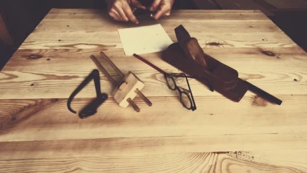 Holzwerkzeug auf der Werkbank. Hände eines Arbeiters aus nächster Nähe. passt Werkzeuge für die Arbeit an.