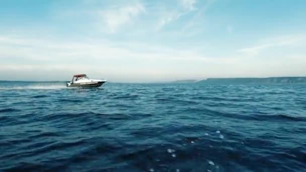 Bewegung mit dem Boot auf dem Meer. Schießen von einer Seite. in der Nähe mit hoher Geschwindigkeit überholt ein großes Boot. Man sieht den fernen Horizont, saubere Luft und Wellen, plätscherndes Wasser. Raum für Text. Stimmungsvolles Video.
