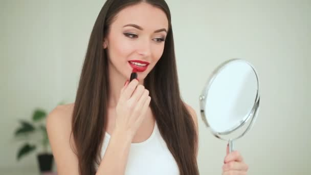 Cosmetics. Woman applying red lipstick.