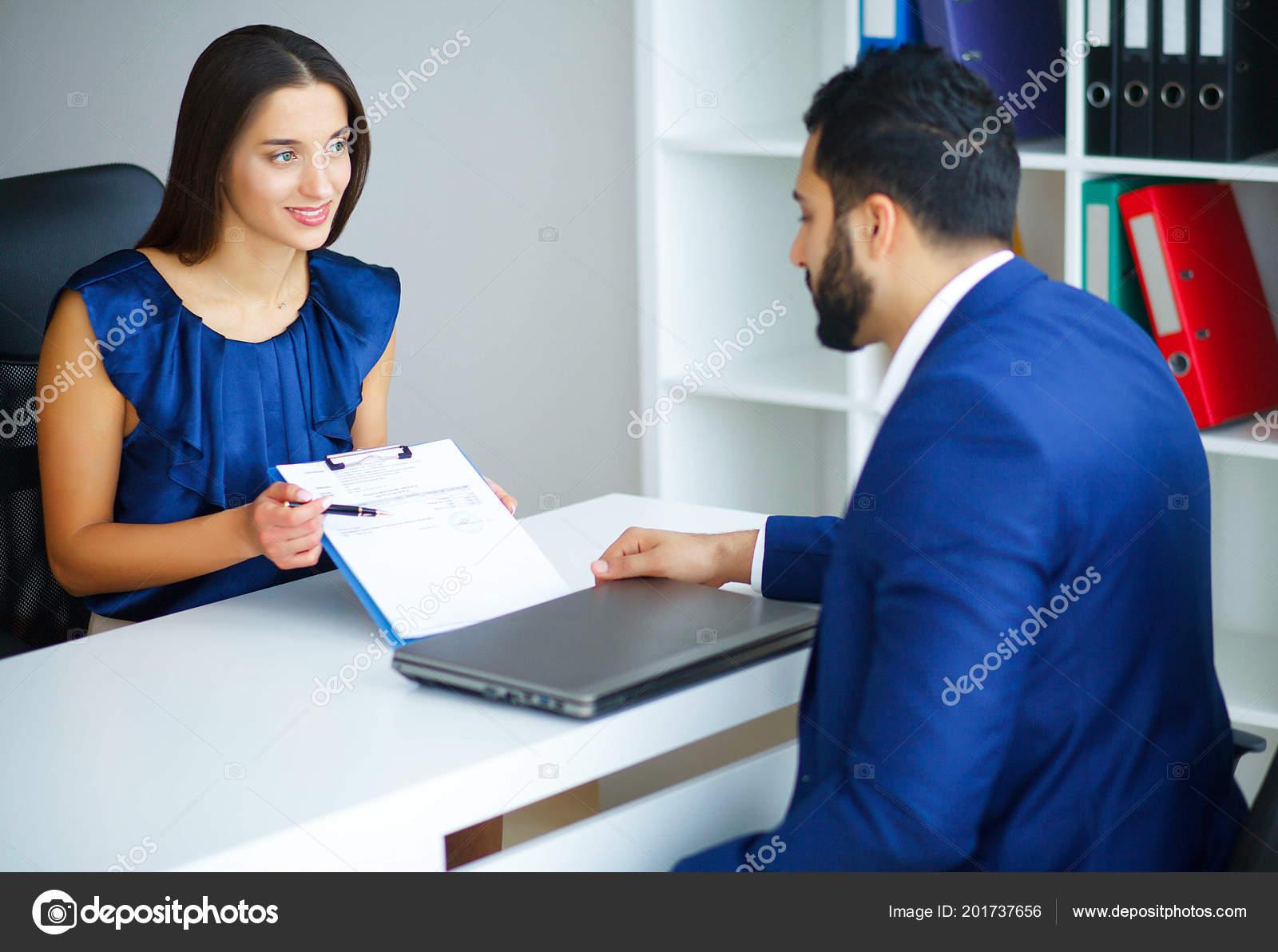 1f221ae11d9f Бизнес. Деловая женщина и бизнес переговоров человек офисе света, сидя за  столом. Женщина, одетая в синяя блуза и юбка бежевого.