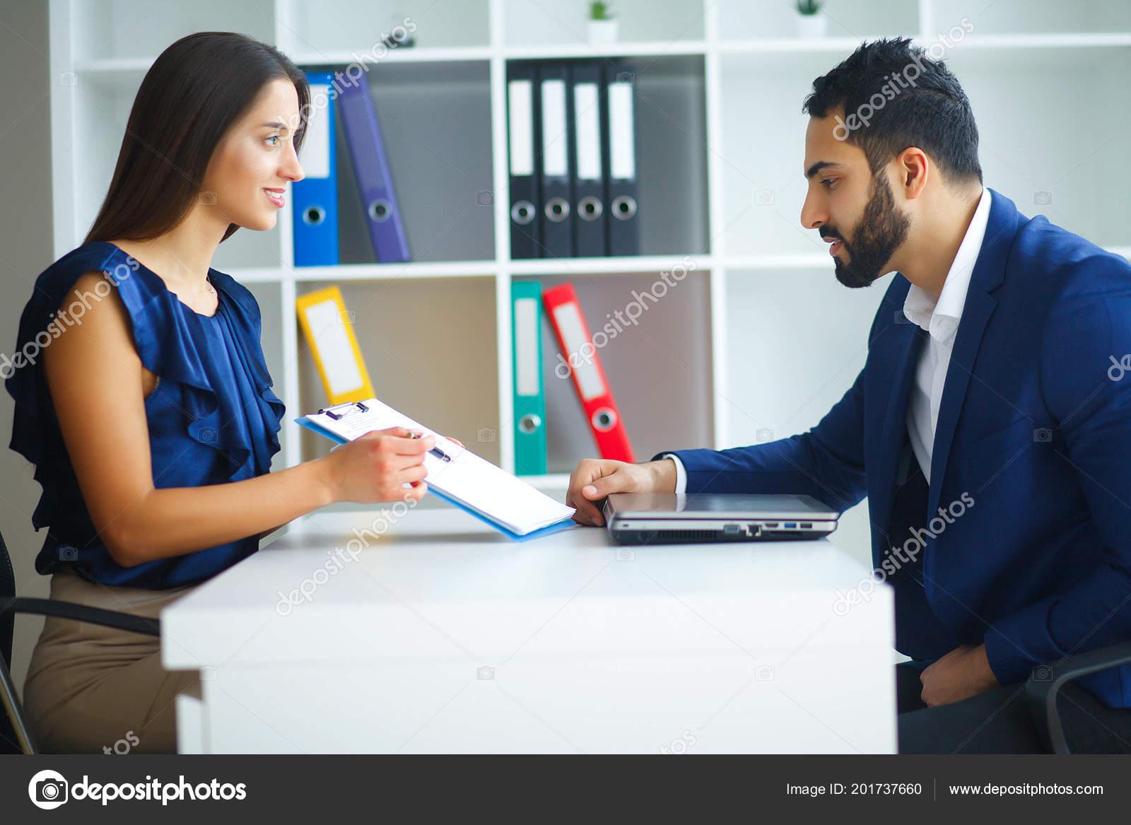 df0b3938af72 Бизнес. Управление бизнес-леди и деловой человек ведет переговоры в отделе  света, сидя за столом. Женщина, одетая в синяя блуза и юбка бежевого.