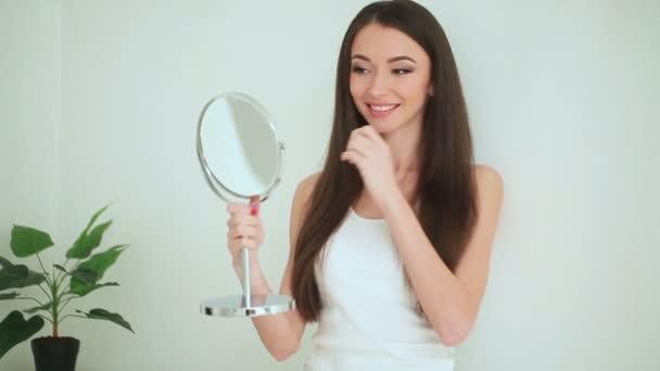 Szépség és a gondozás. Nő alkalmazása krém a bőr. Gyönyörű fiatal nő, tiszta friss bőr érintse meg az arcát. Arckezelés. Kozmetika, szépség- és wellness