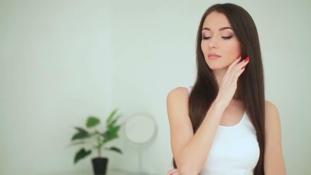 Krása a péče. Žena použití krému na kůži. Krásná mladá žena s čistou svěží pokožku dotýkat její tváře. Ošetření obličeje. Kosmetika, krása a wellness
