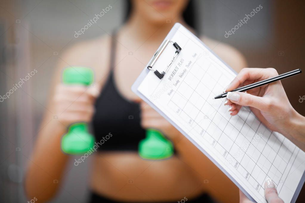 Fitness plan. Sports trainer amounts to workout plan close-up