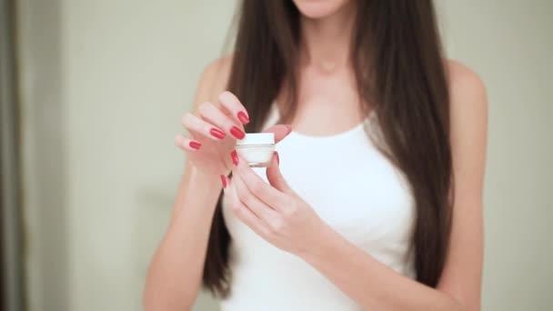 Krásná mladá žena s čistou svěží pokožku dotýkat její tváře. Ošetření obličeje. Kosmetika, krása a wellness