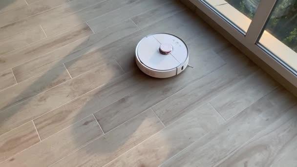 Smart Home. Staubsaugerroboter führt die automatische Reinigung der Wohnung zu einer bestimmten Zeit durch