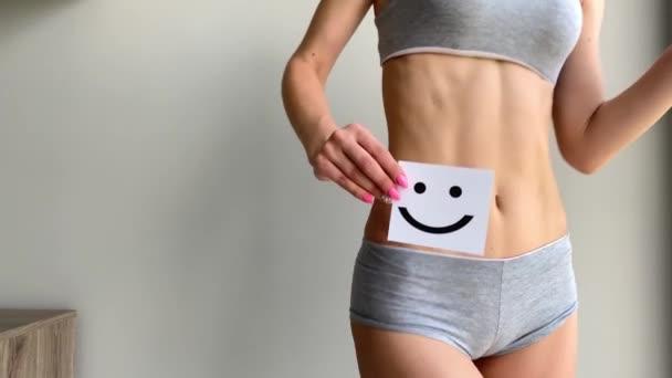 Frauengesundheit. Nahaufnahme einer gesunden Frau mit wunderschönem, schlanken Körper in weißen Höschen, die eine weiße Karte mit einem glücklichen Smiley in den Händen hält. Magengesundheit und gute Verdauung Konzepte. hohe Auflösung