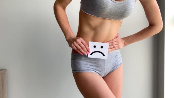Frauengesundheit. Frauenkörper mit traurigem Lächeln in der Nähe des Magens