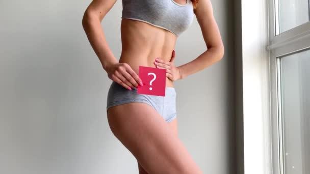 Gesundheit. Frauenkörper in Unterwäsche mit Fragezeichen am Bauch