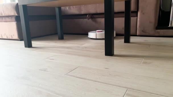 Smart House. Staubsaugerroboter läuft auf Holzboden im Wohnzimmer
