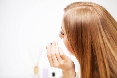 Pretty girl doing facials care procedure in the bathroom