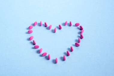 Pink round tablets spread out in the shape of  heart