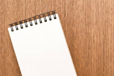 Blank notebook with spiral for the application of labels on wooden background