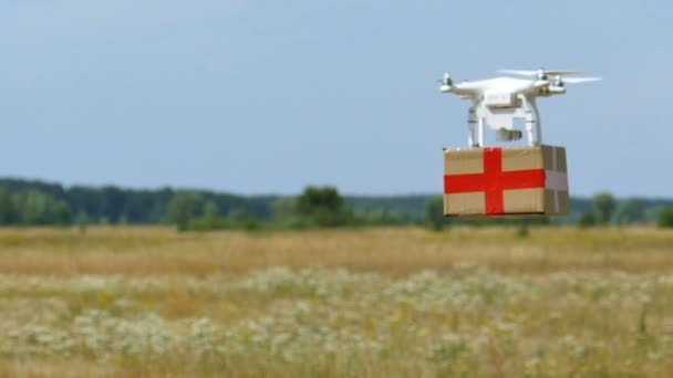 Aerial.  Drone and cargo  box with red cross fly away. Slow motion