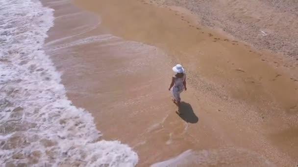 4K  Aerial. Slow Fly around woman in dress , walking summer beach