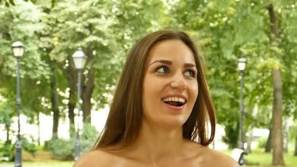 Vonzó, hosszú - haj nő nyári Városligeti séta, és mosolyog, körülnézett. Lassú mozgás, folyamatos lövés