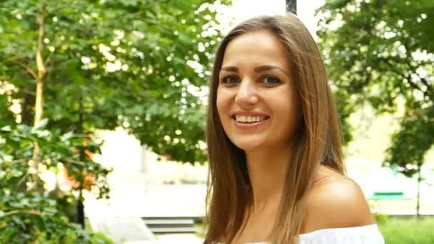 Vonzó hosszú - Városliget nyári haj nő mosolyog a kamera. Lassú mozgás, folyamatos lövés