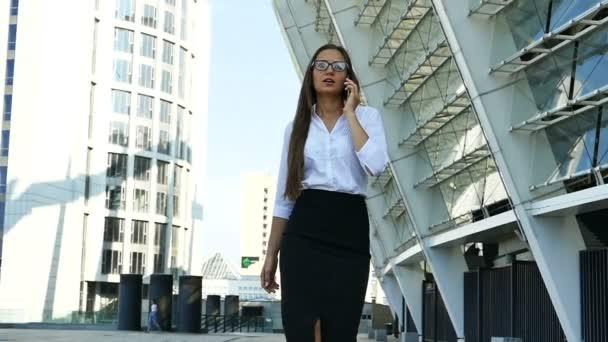 Zeitlupe. seriöse Geschäftsfrau, die in der Bürozone spaziert und mit dem Smartphone spricht