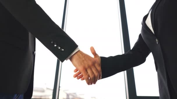 4K.Two business partner, man and woman, shake hands when meeting. Silhouettes of figures