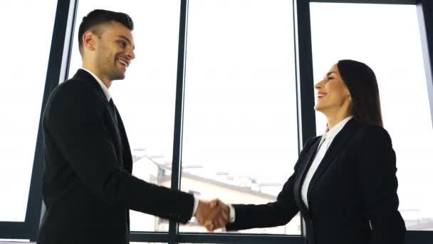 4K.Two business partner, man and woman, with pleasure shake hands when office  meeting.