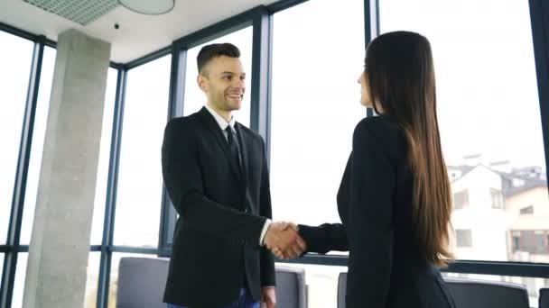 4K. Office  meeting. Two business partner, man and woman, with pleasure shake hands and smile.
