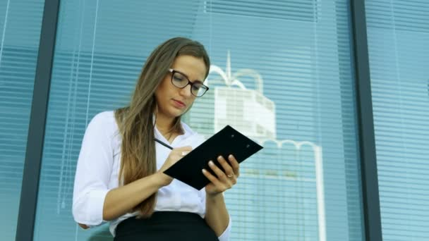 4. Attractive business woman in office zone writes in folder near window and smile.