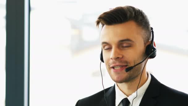 4K .Attentive modern man operator in customer support service center talk by headset.