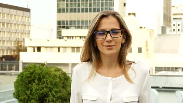 4 k. atraktivní žena v brýlích se dívá na fotoaparát s úsměvem, město obchodní styl. Stabilní záběr
