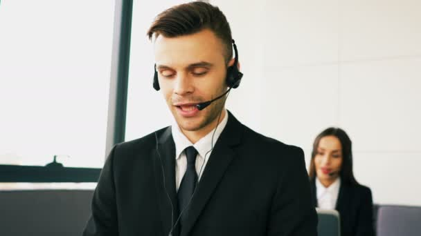4K. Pleasant operators   woman and man in call service center speak with  client .  Woman  smiles , looking  at camera