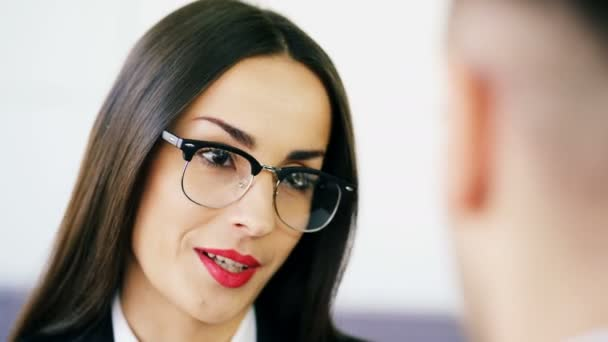 4K. Polite brunette,  business woman , talks in office with man. Face close up in glasses