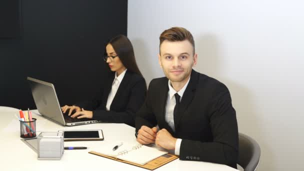 4K.Handsome businessman smiles and shows  finger up to  camera in office area. Woman work at notebook