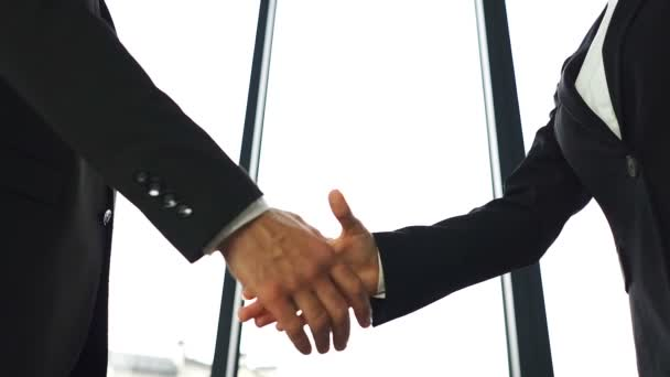 Two business partner, man and woman, shake hands when meeting. Slow motion