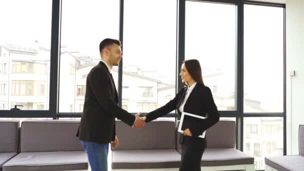 Meeting of business partners. Man and woman shake hands and go.Slow motion