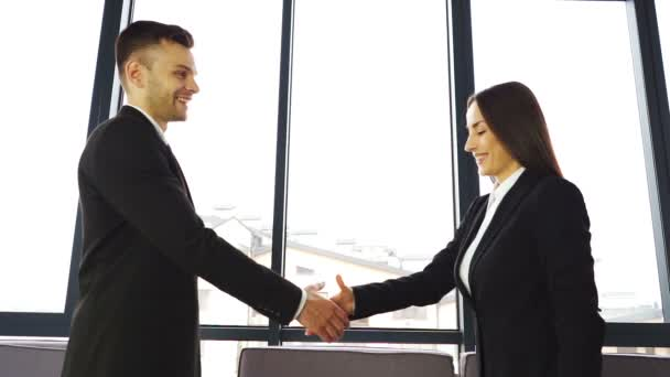 Young man and woman, shake hands when  business meeting in office. Slow motion