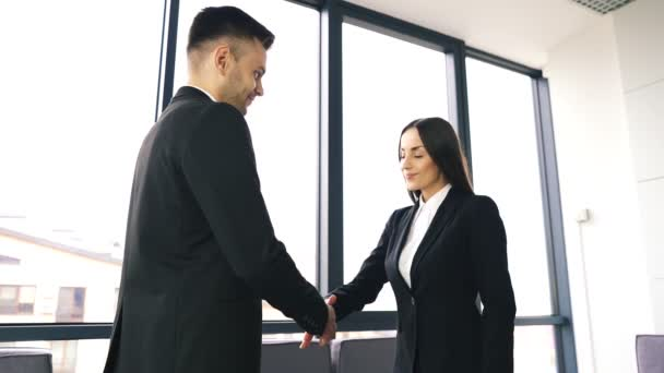 Young man and  smiling woman, shake hands when  business meeting in office. Slow motion