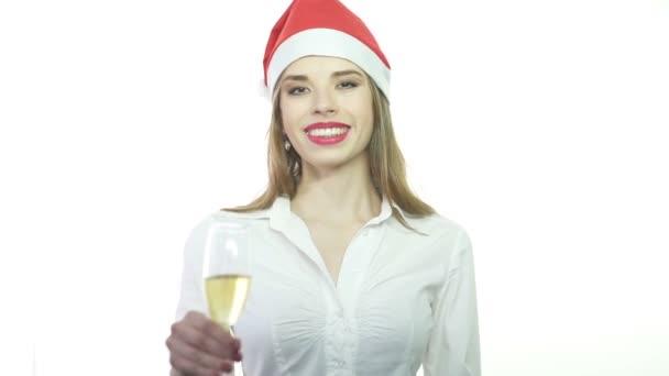Geschäftsfrau mit rotem Weihnachtsmann-Hut lächelt mit einem Glas Champagner. Zeitlupe.